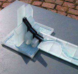 Aus einer Gebäude-Silhouette fließt Wasser in ein geschlängeltes Rinnsal.